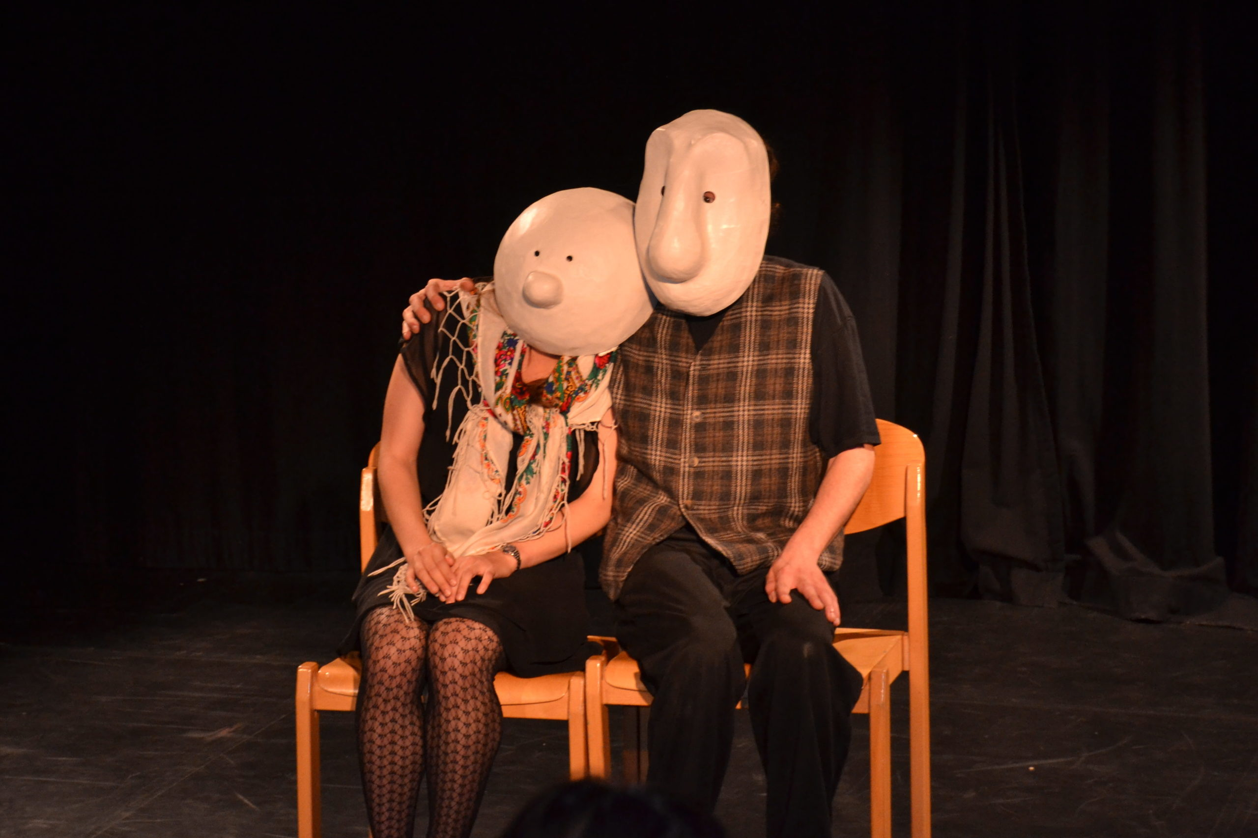Photo de spectacle montrant deux masques larvaires amoureux et enlacés